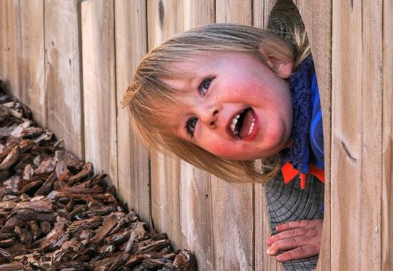 Lachendes Kind in Zaunloch